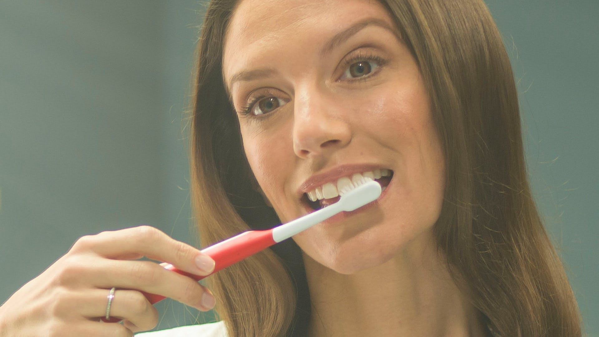 Woman looking into sink holding a toothbrush