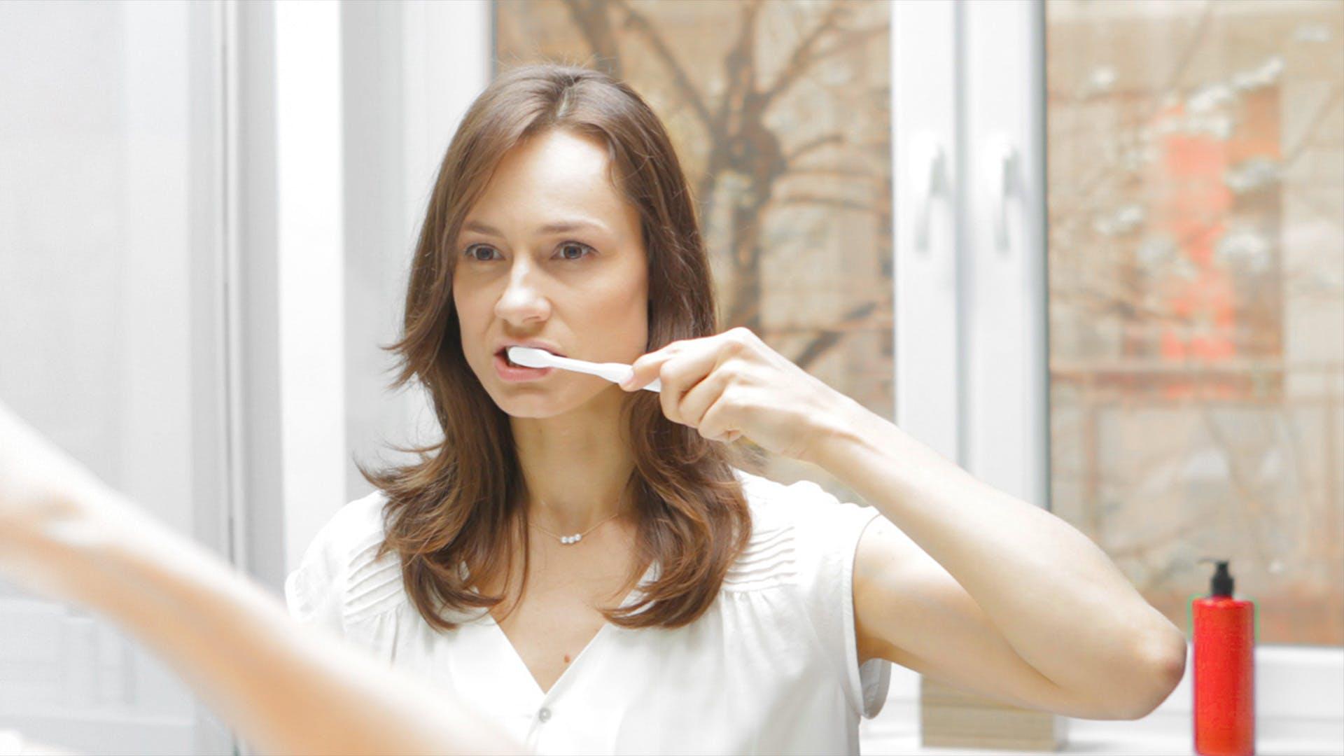 Nainen harjaa hampaita