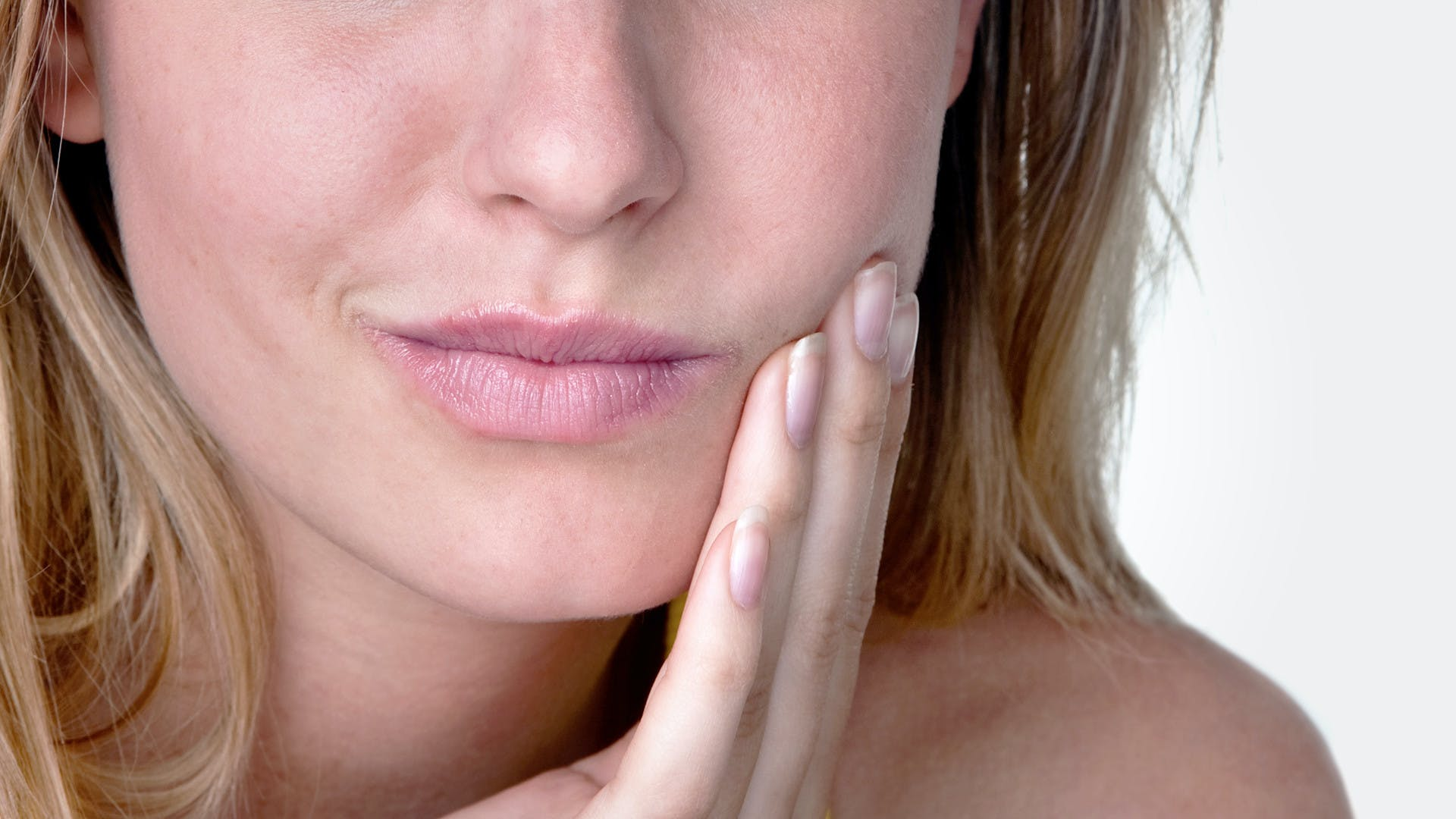 woman with mouth ulcer touching painful mouth and cheek