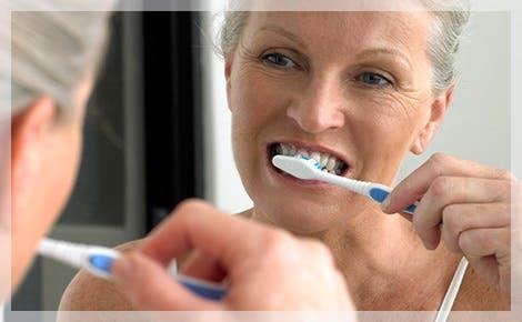 Mujer mayor cepillándose los dientes