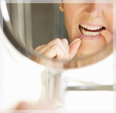 Flossing Teeth In Mirror