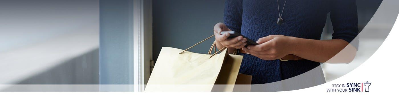 Mujer sosteniendo bolsas y un teléfono