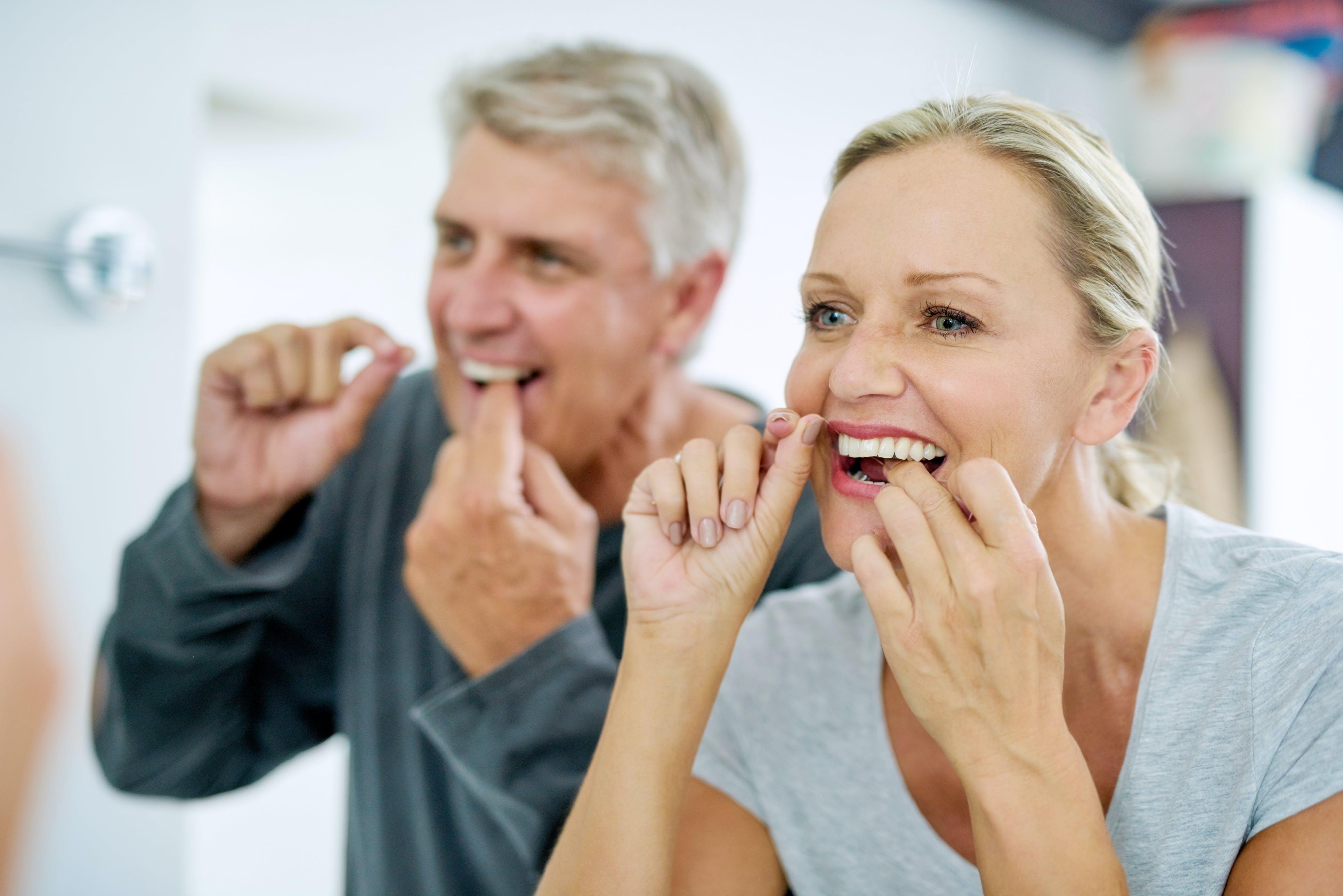 woman looking forward flossing her teeth