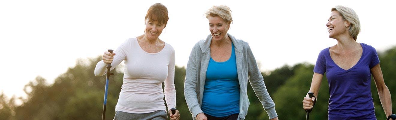 Three women smiling while hiking