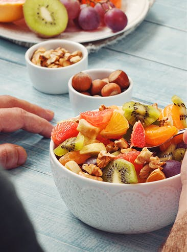 Assiette et petits bols remplis de divers fruits et noix