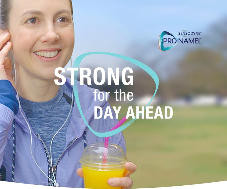 Une femme tenant un verre de jus d'orange dans la main gauche écoutant de la musique