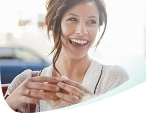 A woman smiling holding a muffin