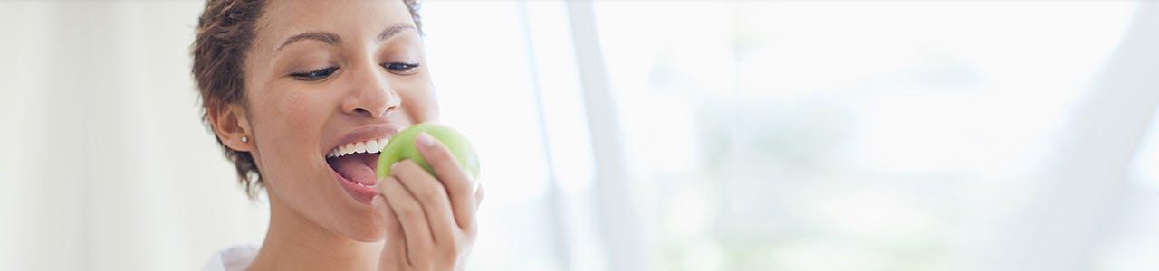 Femme croquant une pomme verte