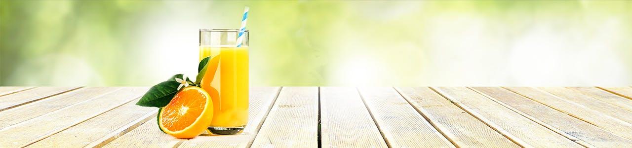 Un verre de jus d'orange et une moitié d'orange sur une terrasse en bois