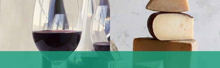Deux verres de vin rouge avec trois morceaux de fromage empilés