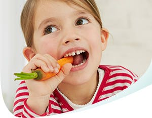 Young girl eating a carrot