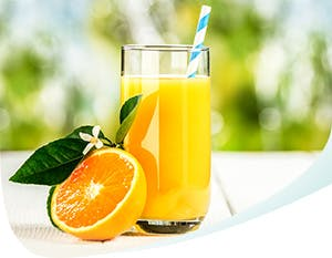 Orange juice in a glass and a half of the orange next to it