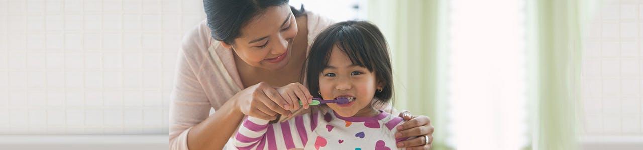 Une mère aide sa fille à se brosser les dents devant le miroir avec Pro-Émail®