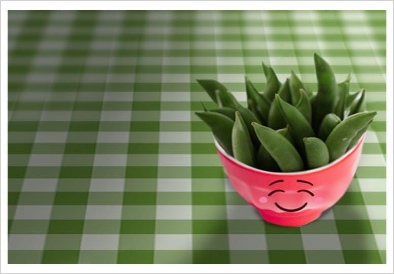 Pois frais en gousse dans un bol rose orné d'un sourire