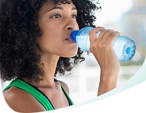 Femme buvant de l'eau en bouteille
