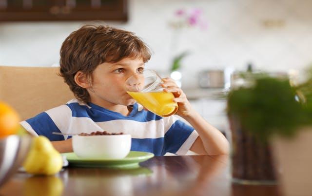 Jeune garçon buvant un grand verre de jus d'orange acide