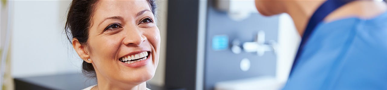 Smiling woman talks to a dental professional