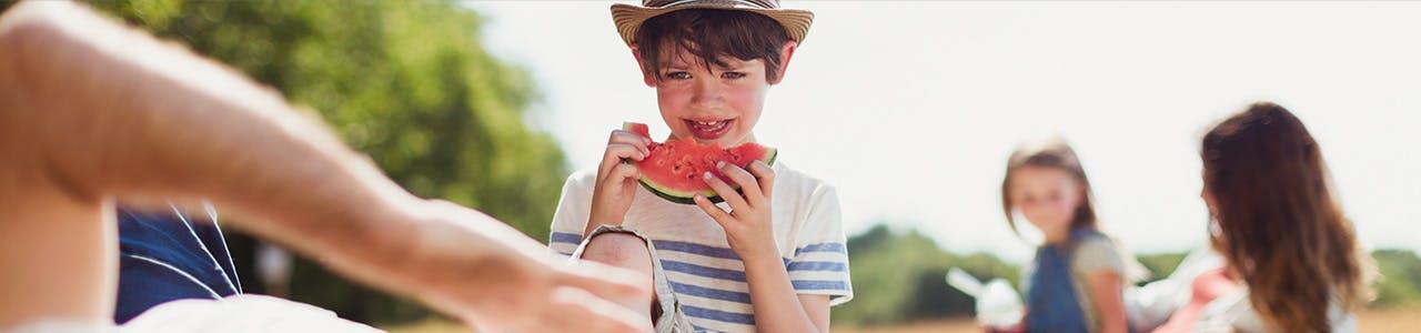 Un garçon mange une tranche de melon d'eau acide tandis que deux fillettes jouent en arrière-plan