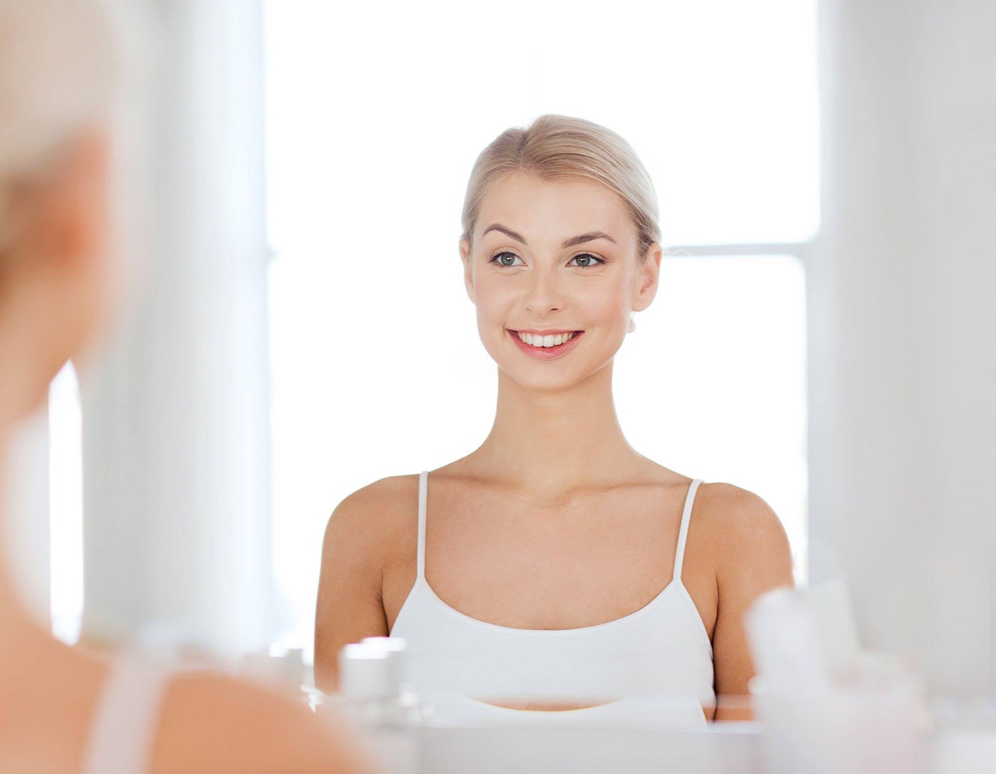 Jeune femme souriante devant un miroir