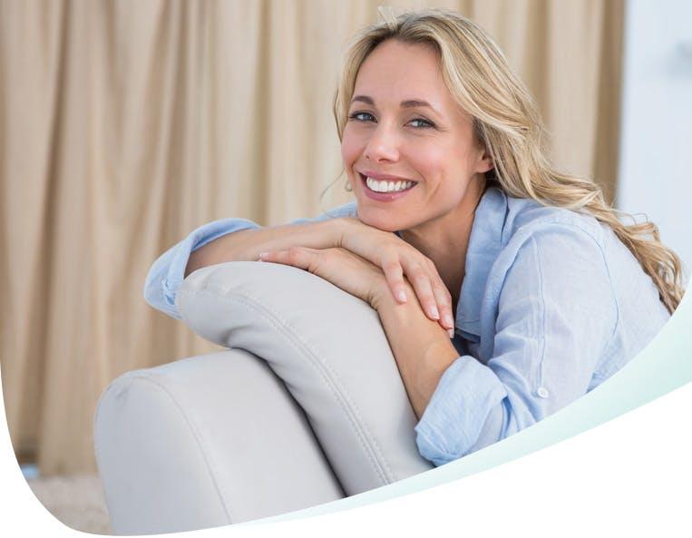 Femme blonde souriante, assise sur un canapé gris, le menton posé sur les mains