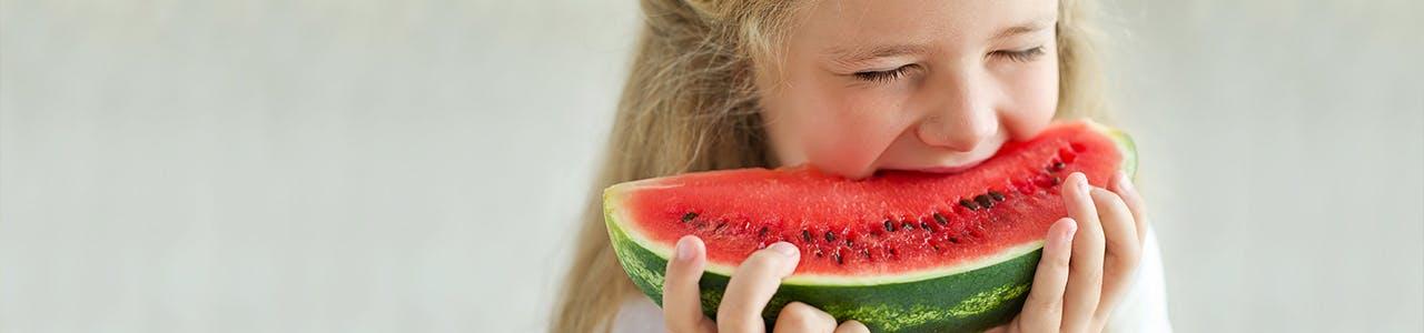 Petite fille en train de mordre dans une tranche de melon d'eau