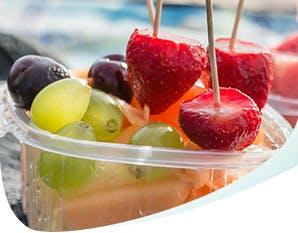 Deux contenants remplis de fruits acides : fraises, raisin, melon