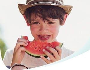 Garçon portant un chapeau mangeant du melon d'eau acide