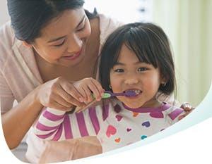 Une mère aide sa fille à se brosser les dents avec Pro-Émail®