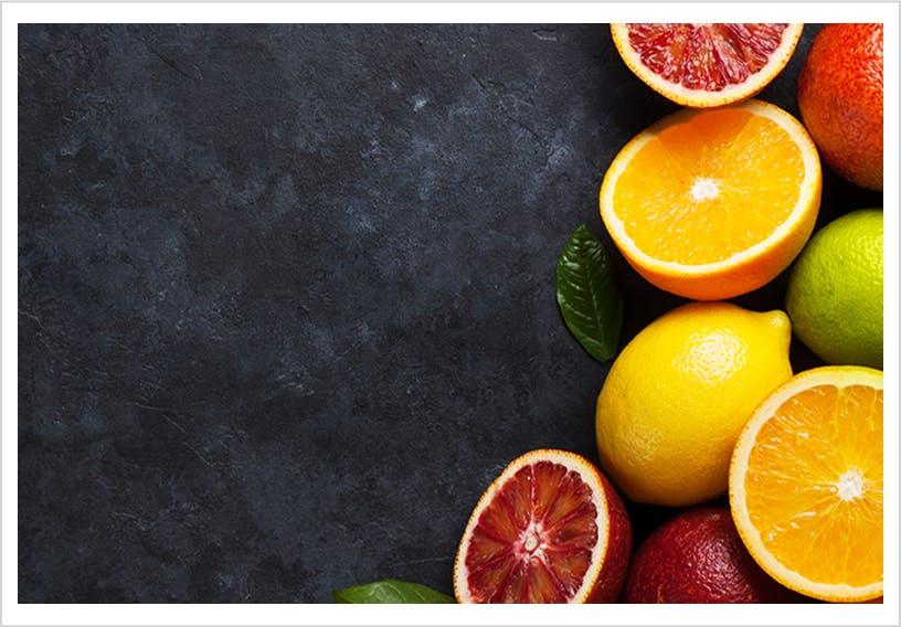 Variété de fruits acides regroupés sur une surface noire