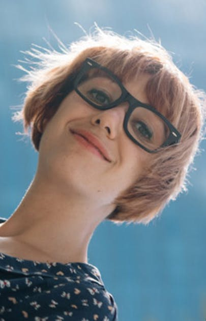 Woman wearing dark rimmed glasses and smiling with a blue sky background