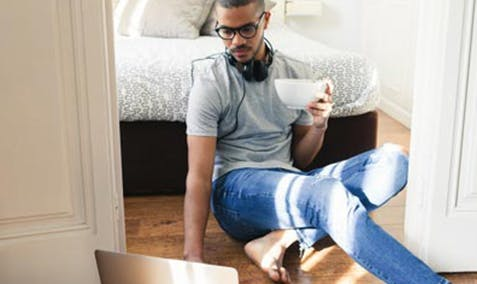 Man sitting in his bedroom, leaning against his bed, drinking a cup of coffee and looking at a laptop