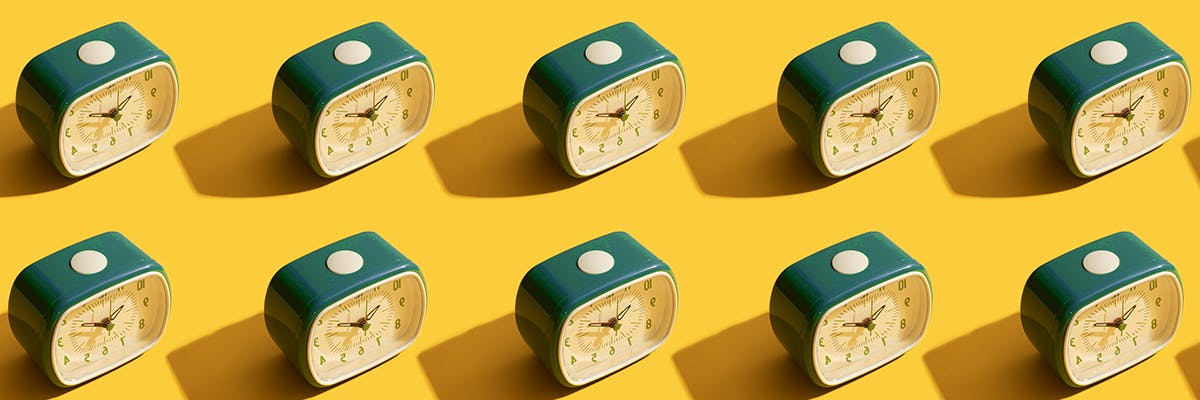 Alarm clocks in a repeating pattern on a yellow background