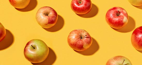 Apples in a repeating pattern on a yellow background