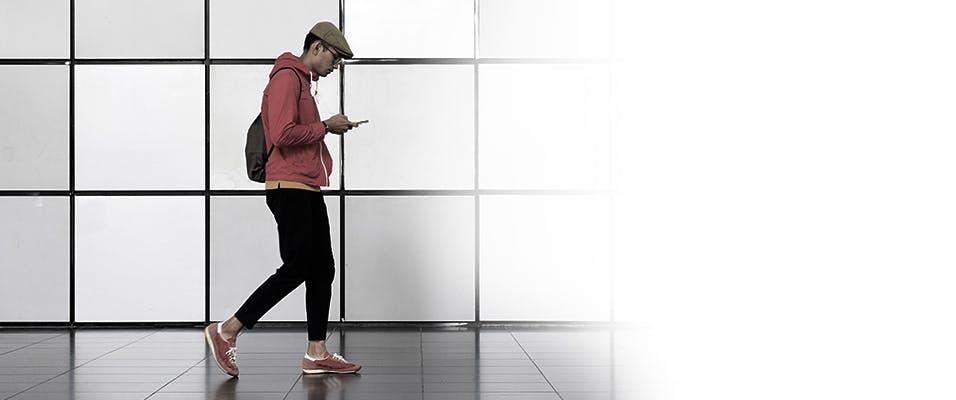 Un homme portant un chandail à capuchon rouge en train de marcher dehors avec un téléphone cellulaire