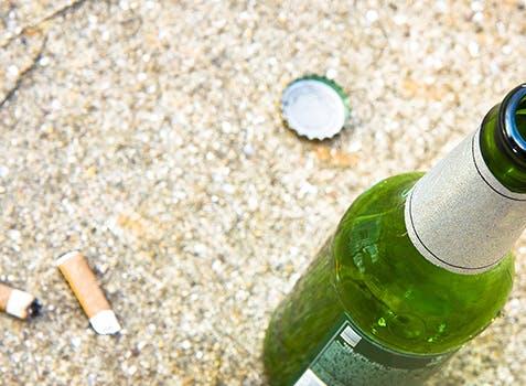 Bouteille de bière sur le sol à côté de 2 mégots de cigarette