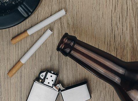 Bouteille de bière vide, cigarette et cendrier sur une table