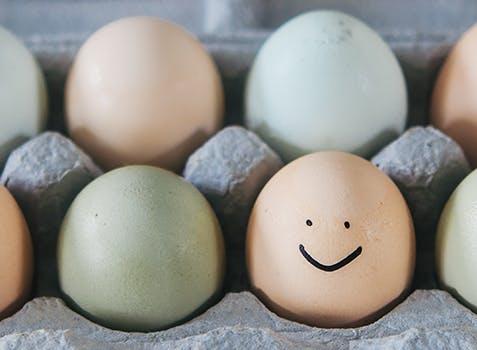Boîte d'œufs; sur l'un d'eux est dessiné un visage souriant