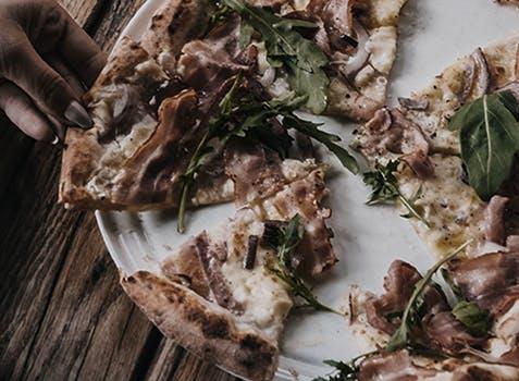 Des mains saisissant des pointes de pizza sur une assiette