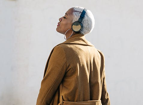 Une femme debout portant un casque d'écoute, la tête tournée vers le ciel et les yeux fermés.