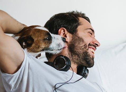 Un homme couché dans son lit, riant pendant que son chien le câline