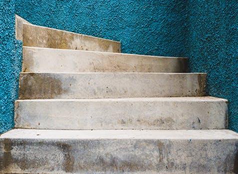 Marches qui montent entre des murs turquoise en stuc