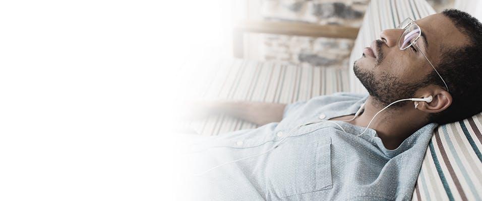Homme allongé sur un futon les yeux fermés qui écoute de la musique avec des écouteurs