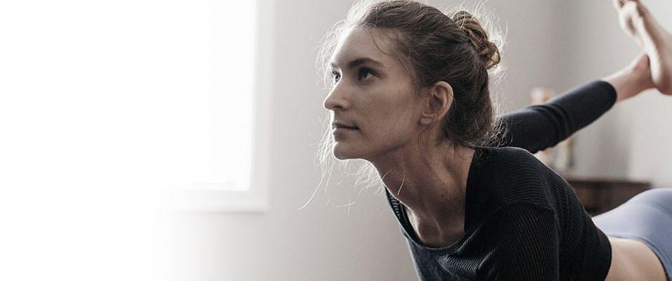 Une femme pratiquant le yoga dans une pièce calme