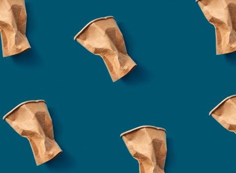 Motif répétitif de gobelets jetables écrasés sur fond bleu