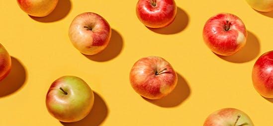 Motif répétitif de pommes sur fond jaune