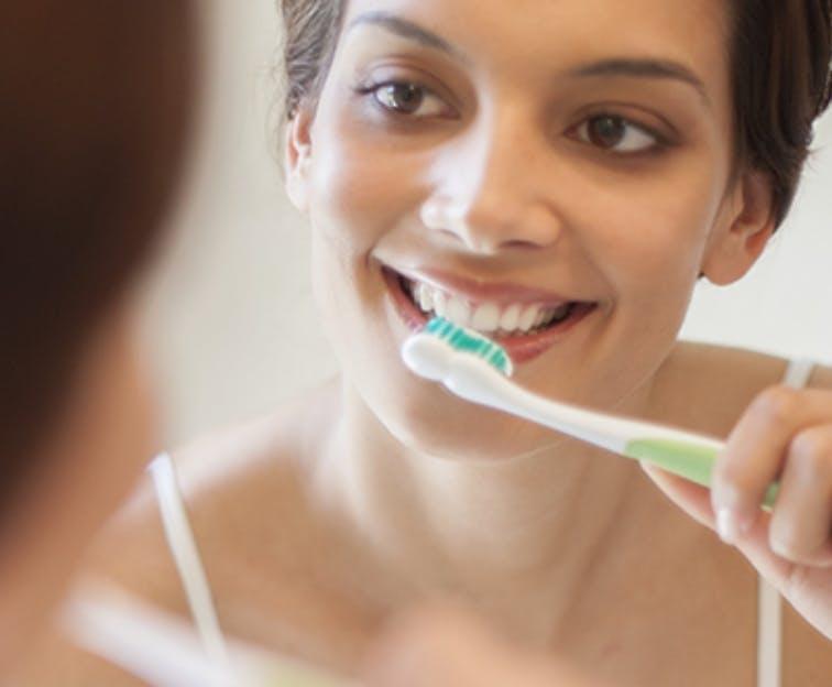 Woman using Sensodyne True White to whiten her sensitive teeth