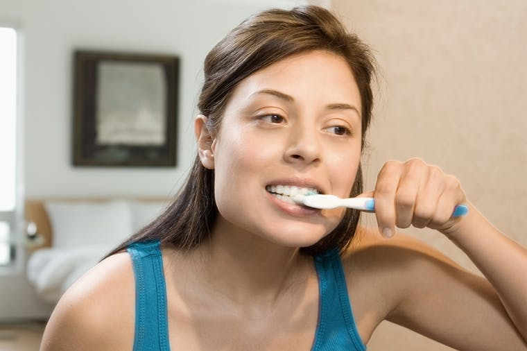 Woman brushing her teeth with sensitivity toothpaste