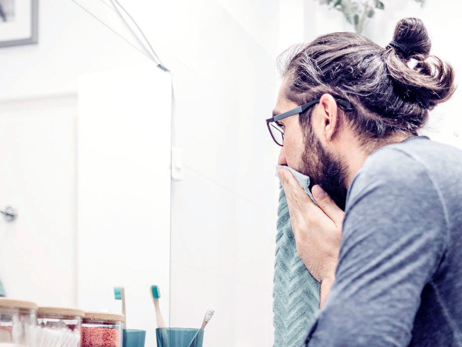 man cleaning face over sink
