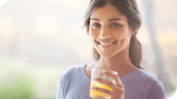Young girl smiling with a drink in her hands
