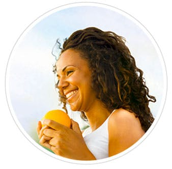 A woman smiling holding an orange in her hands